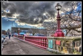 """Este puente es tan viejo como la abadía de Paisley ya que para salvar el río y comunicar mejor la abadía, en el siglo XII se construyó un puente de madera. Aprovechando las fábricas de fundición de hierro locales se crea una nueva estructura de hierro y piedra que ensancha el puente a 70 pies y refuerza la estructura. Es entonces cuando por primera vez se aplica el escudo de la ciudad y una placa que inaugura el puente """"nuevo"""" en 1933."""