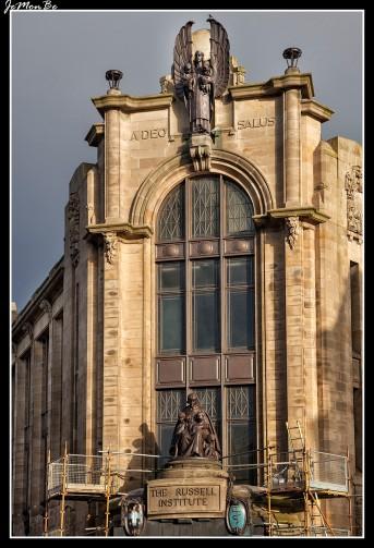 """La señorita Russell hizo construir el edificio como un monumento a sus dos hermanos solteros, Robert y Thomas que habían muerto. El edificio debía ser utilizado como una clínica para los niños del Condado de Renfrew, por lo tanto es un edificio conmemorativo y funcional a un tiempo. Hizo historia arquitectónica con el primer edificio de estructura de hormigón armado en el oeste de Escocia. La puerta principal está coronada por una gran figura maternal en bronce con su progenie flanqueada por dos escudos uno el escudo de armas de Paisley, el otro el símbolo de Esculapio, Dios de la Medicina con una serpiente retorcida alrededor de un bastón. Ambos están en cobre con el esmalte heráldico en color brillante. Por encima de la ventana grande está la masiva figura de bronce de un ángel protector que guarda a la joven generación en sus brazos con el lema A DEO SALUS """"La salud viene de Dios Esta frase esculpida en la obra de piedra."""