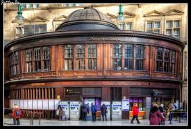 """La estación central de Glasgow fue abierta el 1 de agosto de 1879.La estación fue construida sobre el sitio de la aldea de Grahamston, cuya calle central (calle de Alston) fue demolida para hacer la estación. La gran zona de espera tiene un aspecto muy solemne con comercios laterales todos ellos construidos con maderas de tonos oscuros, muy a tono con el porte exterior del edificio. El Umbrella de Hielanman es un famoso hito en el centro de Glasgow . Es el apodo escocés local para el puente ferroviario amurallado de cristal que une las plataformas de la estación central de Glasgow a través de la calle de Argyle. Con el clima inclemente de la ciudad y la reunión de los montañeses bajo el puente para cobigarse llegó a ser conocido como el paraguas de Hielanman. Por debajo de la """"Umbrella"""" se encuentra una bulliciosa variedad de tiendas y bares, así como el club nocturno """"Arches"""", teatro, galería y restaurante."""