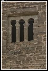 """La iglesia de San Juan de Busa se encuentra en la comarca del Serrablo, en el camino que sube de Olivan a Lárrede. Probablemente, fue iglesia parroquial de un poblado medieval desaparecido. Mandada construir por Ramón Guillén entre 1060 y 1070, es de estilo mozárabe o románico lombardo. No tiene torre de campanario y el ábside no está rematado. Su única nave rectangular está cubierta por un tejado de madera a dos aguas. En el centro del muro orientado al sur, se abre la portada principal. Formada por dos arquivoltas en degradación, la exterior tiene sus dovelas decoradas por una inscripción en caracteres cúficos que dice """"ilaha illa Allah'"""", lo que en árabe significa """"'no hay (otro) dios que Alá""""."""