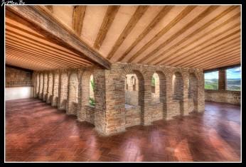 El claustro de la colegiata de Alquezar tiene una forma trapezoidal irregular con un solo ángulo recto, en la unión de crujías sur y sureste; siendo su lado menor el meridional, que cuenta tan solo con tres arcos de medio punto. El mayor se sitúa al sureste y cuenta con diez arcos y enfrente de él la crujía de poniente luce siete arcadas. La crujía norte del claustro la única que resta del momento románico del mismo tiene cuatro arcadas iguales separadas por un machón central. Los cimacios de los capiteles adosados eran de más sencilla hechura que los centrales, mejor decorados. Sus capiteles son dobles, labrados por sus cuatro caras los centrales y en tres en los adosados, con motivos bíblicos. Toda la columnata se alza sobre podio corrido. Las columnas son dobles rematadas por pequeños capiteles con motivos vegetales. Sobre esta estructura descrita, separada por friso de esquinillas, se superpone un segundo piso en ladrillo, cuajado de vanos rematados en arco de medio punto al estilo de los pisos altos de las casonas nobles aragonesas. Las crujías sureste y sur, dejan ver hileras de vanos al exterior del edificio (en la fachada de acceso al edificio, y en la que da vista al caserío del pueblo).