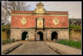 """La Puerta de Gand, construida entre 1617 y 1621, en la antigua muralla española. En la fachada de la entrada a la ciudad tenemos tres partes: la planta baja que tiene tres arcos , la parte media y la parte superior. La parte central está formada por una pared de ladrillo decorada con emblemas rúnicos con un ornamento tallado con el escudo de armas de Lille coronado por un frontón triangular y en ambos lados la ubicación de los brazos del puente levadizo. Encima de cada pasaje lateral hay un cartucho de piedra blanca decorado con varios motivos. La parte superior consiste en un entablamento con una consola central de piedra blanca que tiene un nicho de concha que albergaba una estatua destruida durante un asedio. La fachada de la salida de la ciudad, la planta baja en arenisca está formada por tres arcos forrados con arquivoltas semicirculares .La parte central está formada por una pared de ladrillo de dos colores que forma patrones geométricos y perforada con seis ventanas cruzadas. La parte superior está formada por un techo de pizarra con una claraboya en el centro y dos chimeneas en ambos lados. Alberga el restaurante gastronómico """"Les Remparts"""" desde 1997."""